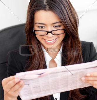 Smiling asian businesswoman reading a newspaper