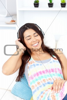 beautiful asian girl with closed eyes listening to music sitting in her sofa