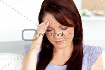 Beautiful woman having a headache sitting on a sofa