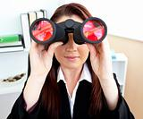 Young businesswoman looking through binoculars sitting at her de