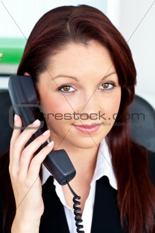 Positive businesswoman phoning in her office