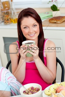 Charming woman eating her breakfast at home holding a cup of cof