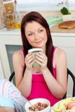 Cute woman eating her breakfast at home holding a cup of coffee