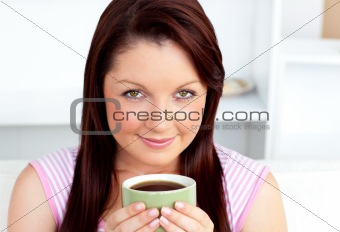 Portrait of an attractive woman holding a cup of coffee at home