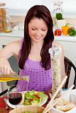 Glowing young woman eating a salad with oil