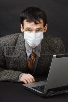 Man in medical mask works in Internet