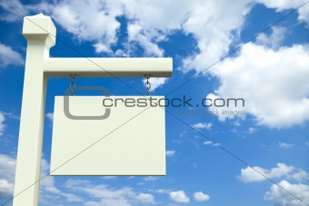 Blank white board in front of a cloudy sky