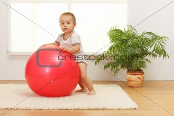 Baby boy with big red ball