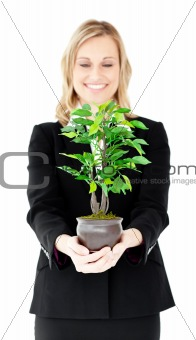Charismatic businesswoman showing a plant at the camera
