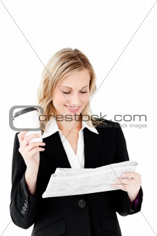 Beautiful businesswoman holding a cup of coffee reading a newspa
