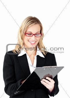 Serious businesswoman wearing glasses taking notes in her clipbo
