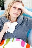 Downcast woman lying on a sofa with tissues and feeling her temp