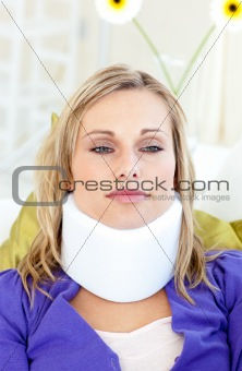 Attractive woman wearing neckbrace lying on a sofa