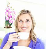 Delighted young woman holding a cup of coffee on a sofa