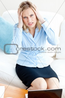 Tired businesswoman sitting on her sofa getting frustrated with