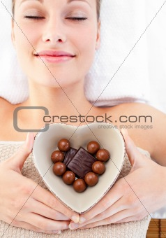 Bright woman holding a bowl in the shape of a heart with chocola