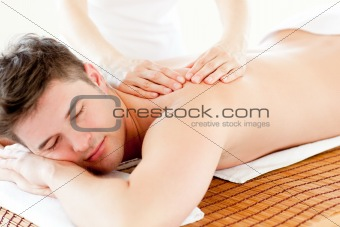 Charismatic relaxed man enjoying a back massage in a spa center