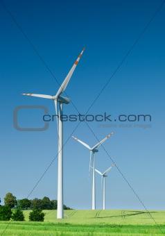 three wind turbines on green field