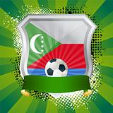 Shiny metal shield on bright background with flag of Comoros
