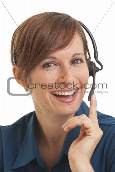 Portrait of smiling young woman telemarketer with hand on headset