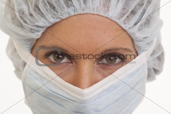 Portrait of serious young woman doctor in scrubs with mask and cap