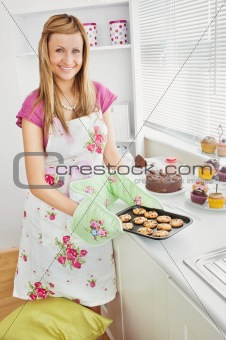 Positive young woman baking cookies in the kitchen