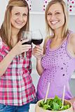 Two radiant women drinking wine after cooking in the kitchen