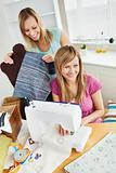 Happy young female friends sewing clothes together at home