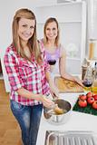 Radiant women cooking spaghetti together in the kitchen