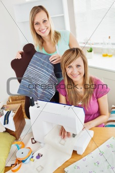 Bright young female friends sewing clothes together at home