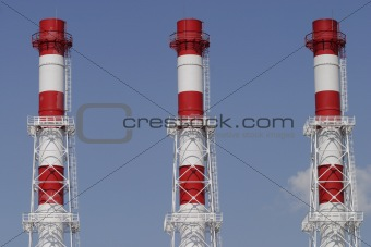 Three industrial color pipes on blue sky