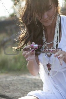 Attractive woman applying nail polish outdoors.