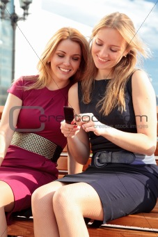 Two smiling girls watching something in mobile phone