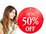 "Bright caucasian woman holding a ""up to 50% off"" red banner"