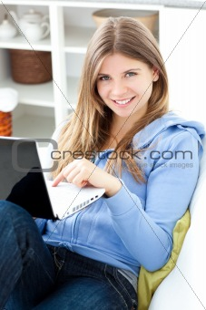Positive woman using a laptop sitting on a sofa