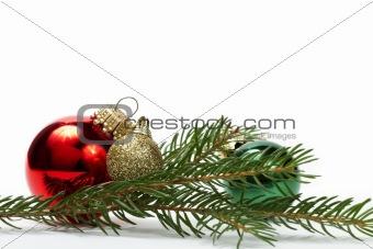 three christmas balls between a branch