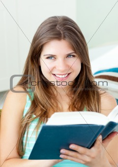 Bright caucasian woman reading a book sitting on a sofa
