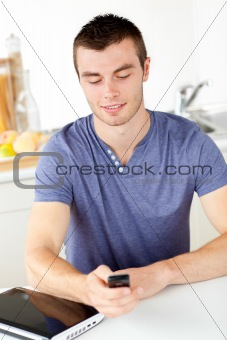 Positive young man sending a text in the living-room
