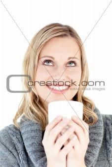 Thoughtful woman enjoying a hot coffee standing