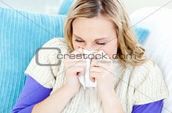 Morbid woman using a tissue sitting on a sofa