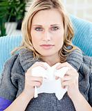 Diseased woman using a tissue sitting on a sofa