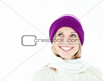 Bright young woman with cap in the winter smiling at the camera