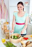Concentrated young woman preparing a salad in the kitchen