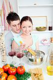 Young couple preparing spaghetti in the kitchen and drinkng wine