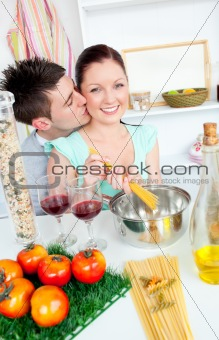 attentive man kissing his girlfriend while cooking together