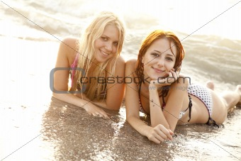 Two beautiful young girlfriends in bikini on the beach