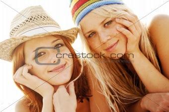 Two beautiful young girlfriends in bikini on the beach