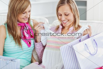 Bright female friends looking at their purchases on a sofa