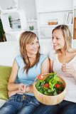 Two female friends eating salad together on a sofa