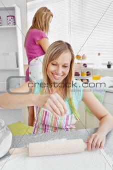 Beautiful young female friends baking pastry in the kitchen